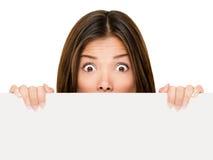 Fahnenzeichenfrau, die über Rand späht Lizenzfreie Stockbilder