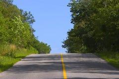Fahrbahn, die einen Hügel cresting ist Lizenzfreie Stockfotografie