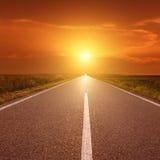 Fahren auf Asphaltstraße bei Sonnenuntergang in Richtung zur Sonne III Stockfotos