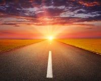 Fahren auf eine leere Asphaltstraße bei Sonnenuntergang stockfotografie