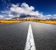 Fahren auf eine leere Asphaltstraße zu den Bergen Stockfotografie