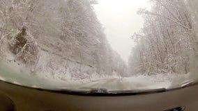 Fahren auf eine schneebedeckte glatte Straße stock footage