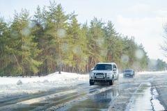 Fahren auf eine schneebedeckte Straße im Winter oder im Vorfrühling Ansicht vom Autofenster auf der Straße mit schmelzendem Schne stockfotografie