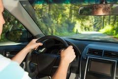 Fahren des Mannes, der innerhalb des Autos im Rotholz, US sitzt Stockfotografie