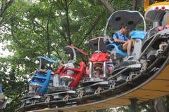 Fahren einer kleinen Achterbahn der Touristen im Shenzhen-Vergnügungspark Stockbild