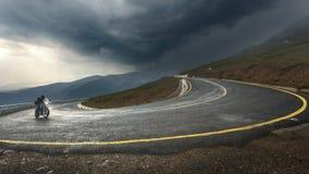 Fahren eines Motorrades auf alpiner Landstraße in Richtung zum Sturm Lizenzfreie Stockfotografie