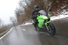 Fahren eines Motorrads im schlechten Wetter Stockbild