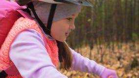 Fahren kaukasische Fahrten der Kind eins Straße im Herbstpark rad Schwarzer orange Zyklus des kleinen Mädchens Reitim Waldkind ge stock video