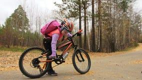 Fahren kaukasische Fahrten der Kind eins Straße im Herbstpark rad Schwarzer orange Zyklus des kleinen Mädchens Reitim Waldkind ge stock footage