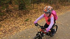 Fahren kaukasische Fahrten der Kind eins Straße im Herbstpark rad Schwarzer orange Zyklus des kleinen Mädchens Reitim Waldkind ge stock video footage