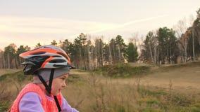 Fahren kaukasische Fahrten der Kind eins Straßenbahn im Schmutzpark rad Orange Zyklus des Mädchenreitschwarzen in der Rennbahn Ki stock video footage