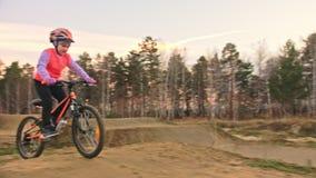 Fahren kaukasische Fahrten der Kind eins Straßenbahn im Schmutzpark rad Orange Zyklus des Mädchenreitschwarzen in der Rennbahn Ki stock video