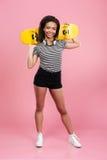 Fahren lächelnde afrikanische Jugendlichestellung und -holding der Junge Skateboard Stockfoto