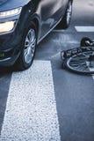 Fahren Sie das Lügen nahe bei einem Auto auf dem Fußgängerübergang rad Stockbilder