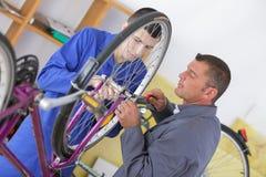 Fahren Sie den Mechaniker und Lehrling rad, die Fahrrad in der Werkstatt reparieren lizenzfreies stockfoto