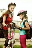 Fahren Sie den Reifen rad, der mit dem Kinderradfahrer Mädchen-Reparaturfahrrad auf Straße pumpt Stockbild