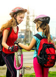Fahren Sie den Reifen rad, der mit dem Kinderradfahrer Mädchen-Reparaturfahrrad auf Straße pumpt Stockfotografie