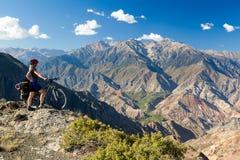 Fahren Sie den Reisenden rad, der an der Klippe steht und Bergblick genießt Lizenzfreie Stockfotos