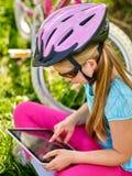 Fahren Sie den tragenden Sturzhelm des Mädchens rad, der am Tabletten-PC beim Radfahren aufpasst Lizenzfreie Stockbilder