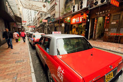 Fahren Sie die Autos mit einem Taxi, welche auf die Passagiere auf beschäftigter Stadtstraße mit vielen Speichern in Hong Kong wa Stockfotos