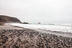 Fahren Sie die Küste entlang, bewegen Sie, Strand und ein großer Felsen wellenartig Stockbild