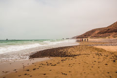 Fahren Sie die Küste entlang, bewegen Sie, Strand und ein großer Felsen wellenartig Stockfotografie
