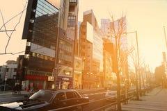 Fahren Sie in die Straße im Roppongi-Bereich in den Strahlen des Sonnenuntergangs, Tokyo, Japan mit einem Taxi Stockfotos