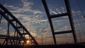 Fahren Sie durch das Brige im Bau mit drastischen Wolken und der untergehenden Sonne Sonnenuntergang stock video