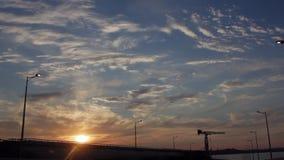 Fahren Sie durch das Brige im Bau mit drastischen Wolken und der untergehenden Sonne Sonnenuntergang stock footage