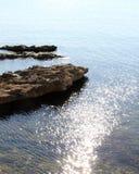 Fahren Sie Linie, mit Felsen und Wasserreflexionen die Küste entlang Stockfoto