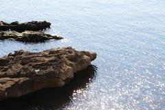 Fahren Sie Linie, mit Felsen und Wasserreflexionen die Küste entlang Stockbilder