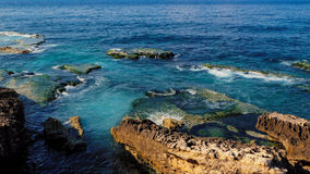 Fahren Sie mit Felsen an am Meer, blauen und Smaragd farbigen dem Wasser des freien Raumes die Küste entlang Stockfotos
