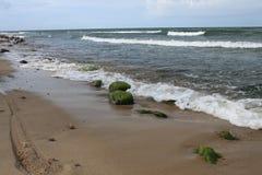 fahren Sie Reifenbahnen und -steine auf dem Strand, Polen rad Lizenzfreie Stockfotos