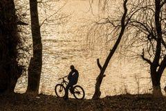 Fahren Sie Reiter am Rand eines Flusses rad, der den Sonnenuntergang betrachtet Sepiafarben Stockbild