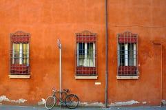 Fahren Sie vor altem orange Gebäude rad Stockfotografie