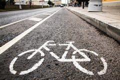 Fahren Sie weißes Zeichen oder Ikone auf der Asphaltstraße in der Stadt rad stockbilder