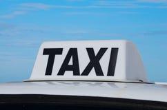 Fahren Sie Zeichen auf Autonahaufnahme mit blauem Himmel mit einem Taxi Lizenzfreies Stockbild