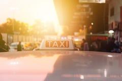Fahren Sie Zeichen auf dem Dach des Taxis auf der verkehrsreichen Straße über gelb-orangeem Erwärmungssonnenunterganghintergrund  Lizenzfreie Stockfotos