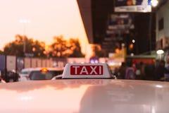 Fahren Sie Zeichen auf dem Dach des Taxis auf der verkehrsreichen Straße über gelb-orangeem Erwärmungssonnenunterganghintergrund  Stockbilder