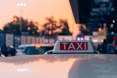 Fahren Sie Zeichen auf dem Dach des Taxis auf der verkehrsreichen Straße über gelb-orangeem Erwärmungssonnenunterganghintergrund  Lizenzfreies Stockfoto