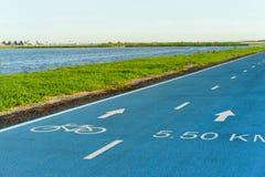 Fahren Sie Zeichen auf der Straße mit blauem Himmel rad: Fahrradweg Stockbild