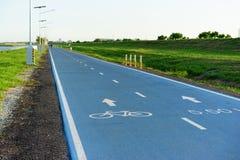 Fahren Sie Zeichen auf der Straße mit blauem Himmel rad: Fahrradweg Stockfotografie