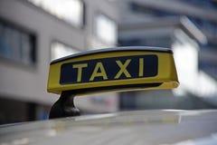 Fahren Sie Zeichen auf einem Auto in der Großstadt am Tag, Abschluss oben mit einem Taxi Lizenzfreie Stockfotos