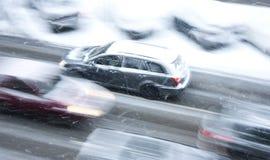 Fahren von Autos auf der schneebedeckten Stadtstraße in der Bewegungsunschärfe Lizenzfreie Stockfotos
