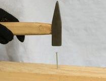Fahren von Nägeln im Brett stockfoto