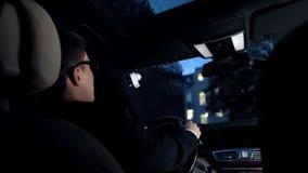 Fahrer, der im Luxusauto am regnerischen Wetter, Nachtzeit-Antrieb, Unfallrisiko sitzt lizenzfreies stockfoto