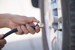 Fahrer, der Luftdruck überprüft und Luft in den Reifen füllt lizenzfreie stockfotografie
