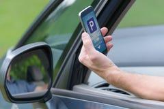 Fahrer, der Smartphone App verwendet, um für das Parken zu zahlen stockfoto