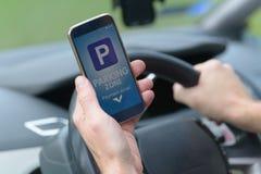 Fahrer, der Smartphone App verwendet, um für das Parken zu zahlen lizenzfreie stockfotos