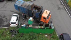 Fahrer des Müllwagens städtischen Behälter mit Abfall in seine Behälter beladend stock footage